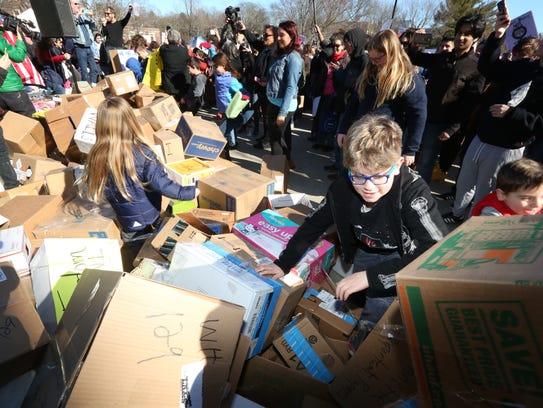 A wall of cardboard boxes is symbolically knocked down