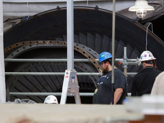 Contractors work on the steam turbines during a routine
