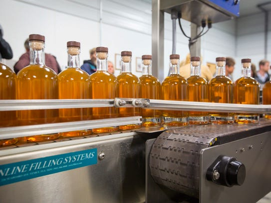 Filled bottles of Templeton Rye wait to be labled and
