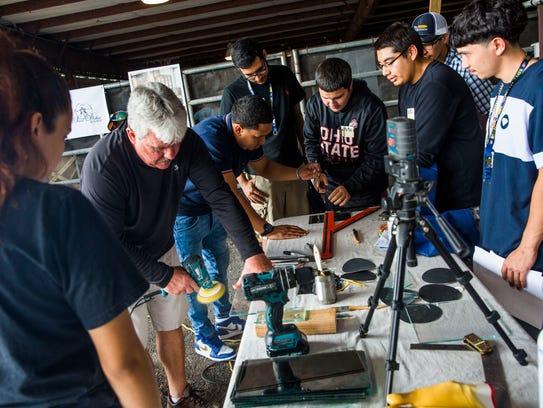High school students watch a glass-cutting demonstration