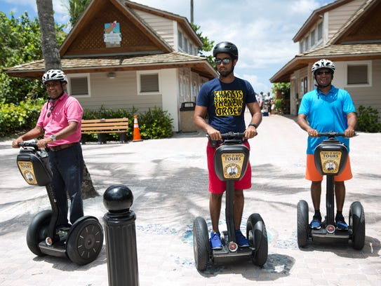 Bipin Patel, from left, Malak Patel, and Rajesh Patel, all of Ocala, make a short stop at the Naples Pier during their tour offered by Segway Tours of Naples in August 2016.