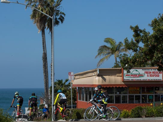 Cyclists pass Don Bravo Mexican Grill and Cantina in