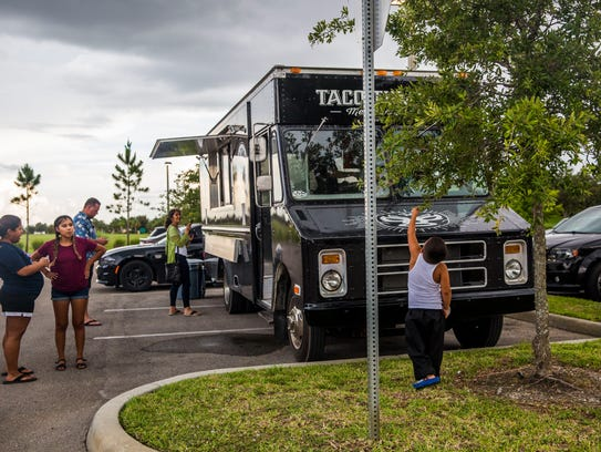 People wait for their food outside of the new taco