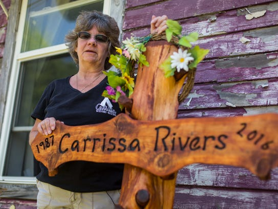 Catherine Rivers stands next to a cross in her from