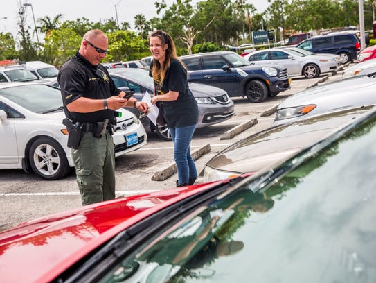 Sergeant Thad Rhodes talks with Jodie Stout of Naples