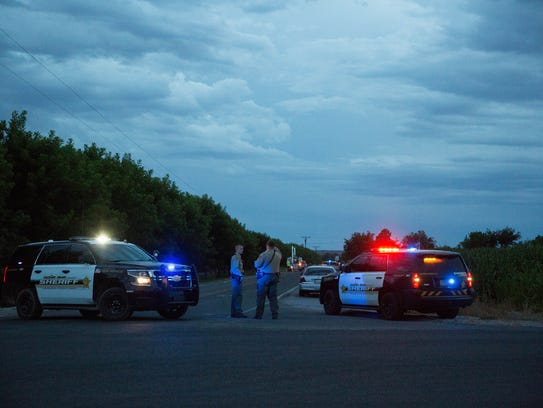 Doña Ana County Sheriff's deputies stand guard on Highway