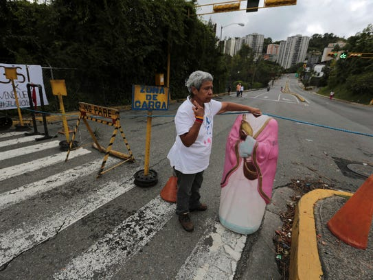A woman builds a road barricade to protest against
