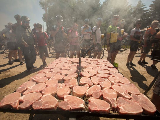 Cyclists wait in line for pork chops being cooked by Mr. Pork Chop in Curlew, Iowa, on July 24, 2017, the second day of RAGBRAI 2017.