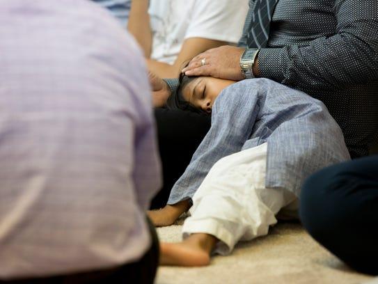 A young boy falls asleep during Friday's prayer service,