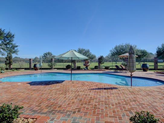 The pool is surrounded by beautiful landscaped grounds