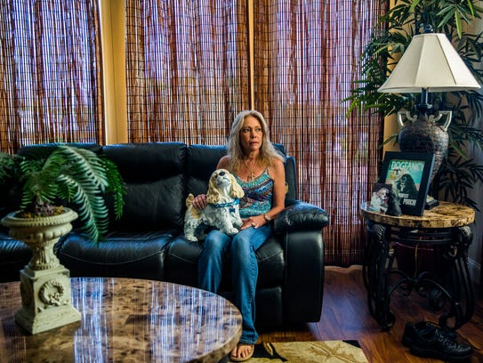 Becky Ebert holds a statue in memory of her late dog,
