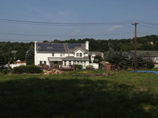A house with solar panels is across the road from Marian