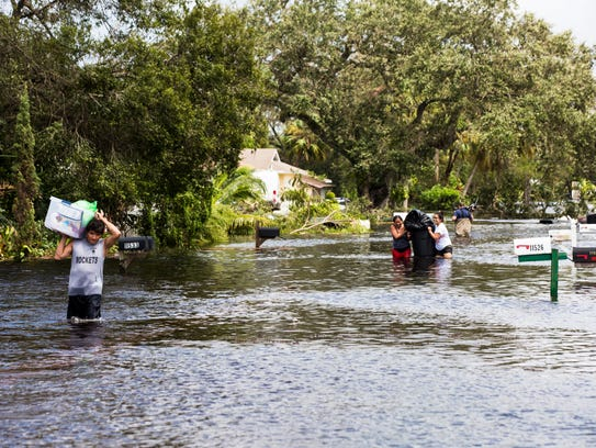 Residents carry their belongings through floodwaters