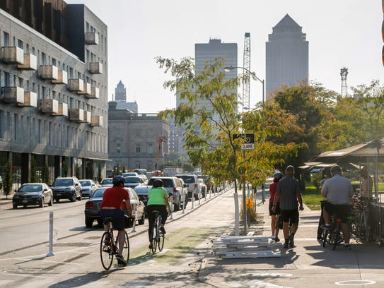 Cyclist ride the new protected bike lanes on East Grand