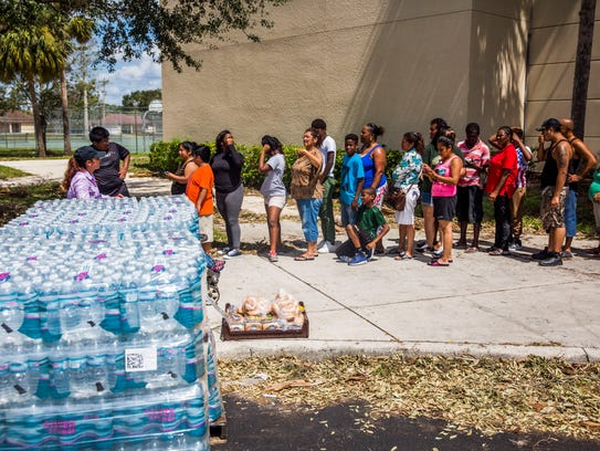 People wait in line for food and water from Collier