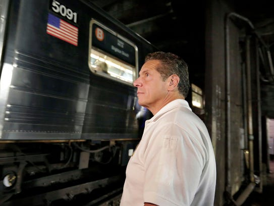 Gov. Andrew Cuomo watches a subway train pass in the