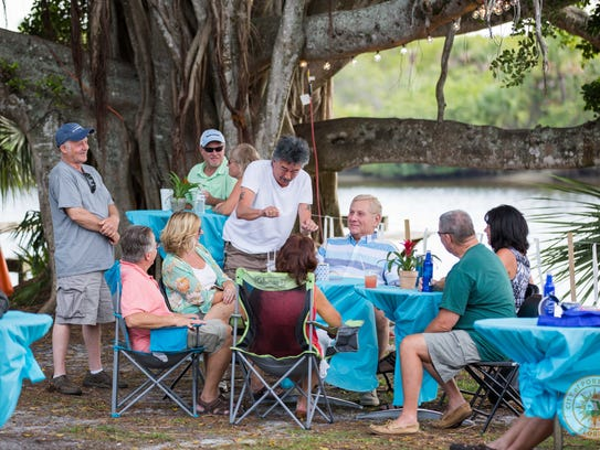 Visitors relax near the St. Lucie River at Port St.