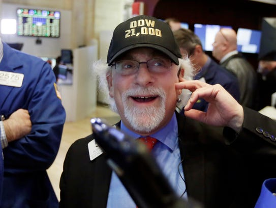 "Trader Peter Tuchman wears a ""Dow 21,000"" hat as he"