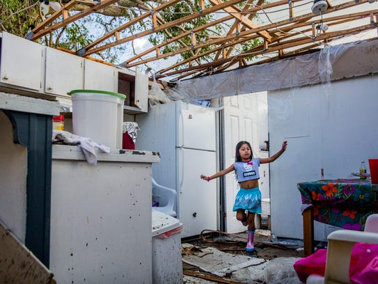 Maria Romero, 6, steps over debris in her home the