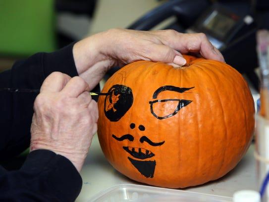 "Joanna ""Ginger"" Cardilli paints a pirate on a pumpkin"