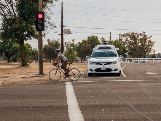 A Waymo self driving minivan stops for a cyclist at