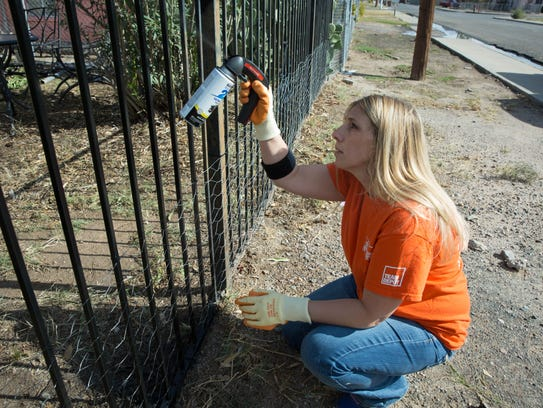 Alyssa Boy, a volunteer from Home Depot, spray paints the fence around Frances Madrid's home Thursday, November 9, 2017. The group of volunteers helping renovated Madrid's home are part of a program that go out and help veterans and their families.