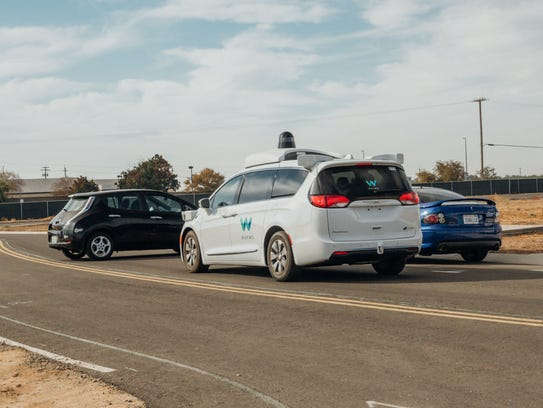 A Waymo minivan outfitted with self-driving sensors