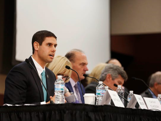 Nate Boulton (left) answers a question as candidates
