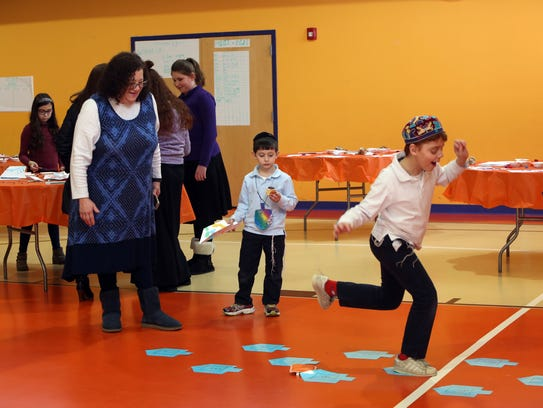 Pre-school director Mindy Mandel-Werner looks on as Levy Froimovich, 9, tries the dreidel hopscotch during the Hanukkah expo at the Hebrew Academy in New City.