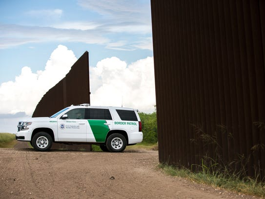 Border Patrol vehicles beside the border wall in Brownsville,