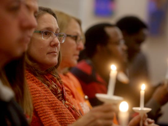 Nicole Lesser of Hastings-on-Hudson, N.Y. holds a candle