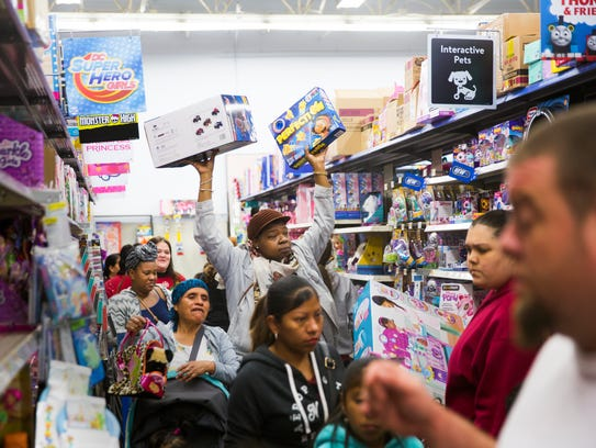 Coretta L. holds toys above her head as she navigates an aisle during the Joy of Giving event Saturday, Dec. 16, 2017, at a Walmart on Collier Boulevard in East Naples. Hundreds of Collier County families were able to spend $100 for each child, starting at 6 a.m.