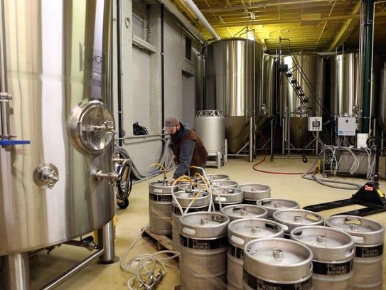 Brewmaster Mike McManus fills kegs at the Industrial