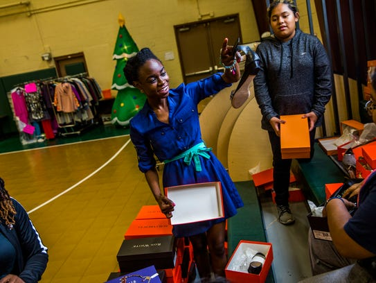 Wotts Mercy, 25, organizes donated shoes at Pace Center