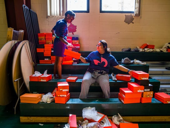 Wotts Mercy, 25, organizes donated shoes with students