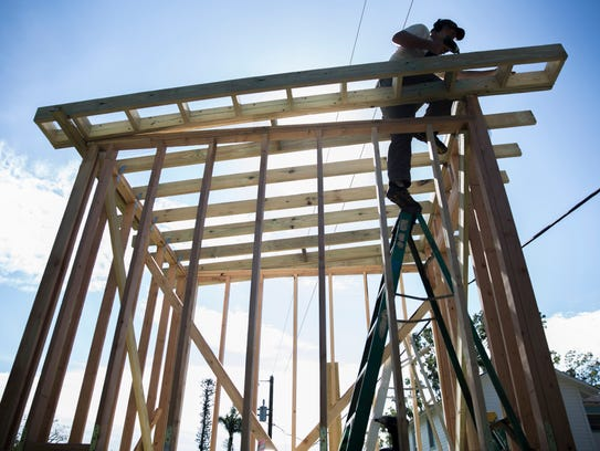 Bobby Bonnet, 62, works on securing the roof beams