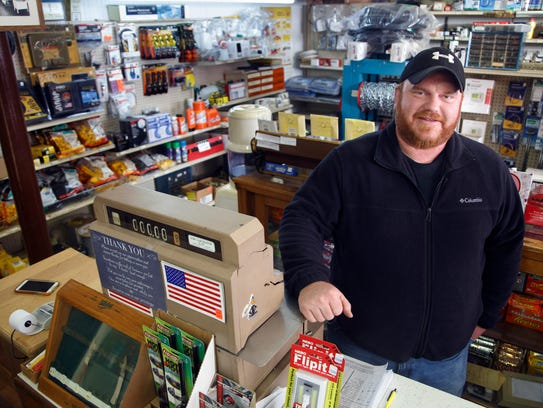 Ben Speck stands at the register of his hardware store