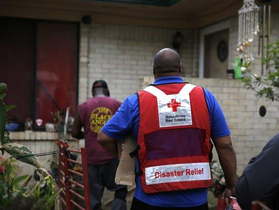 Red Cross volunteer Ralph Campbell, right, follows