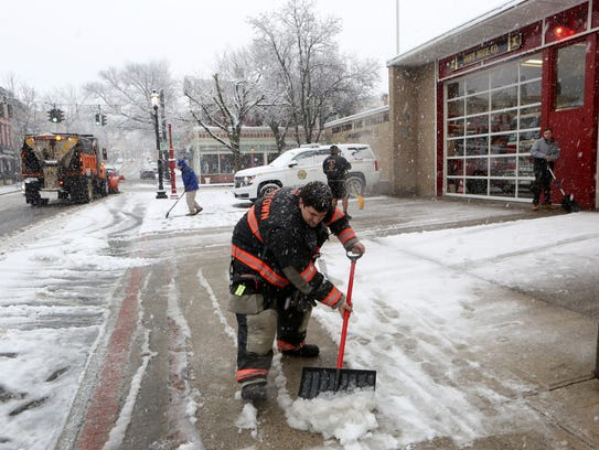 2:14 p.m. Volunteer firefighters clear the snow in