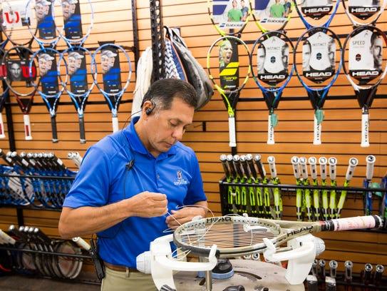 Tennis associate Angel Gutierrez strings a customer's
