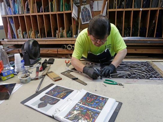Miguel Reyes, gets ready to solder a stained glass