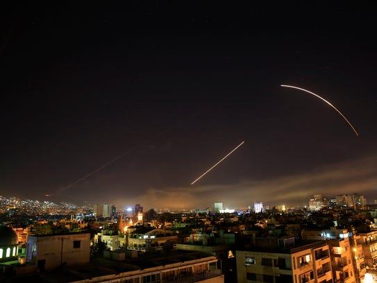 Missiles streak across the Damascus skyline.