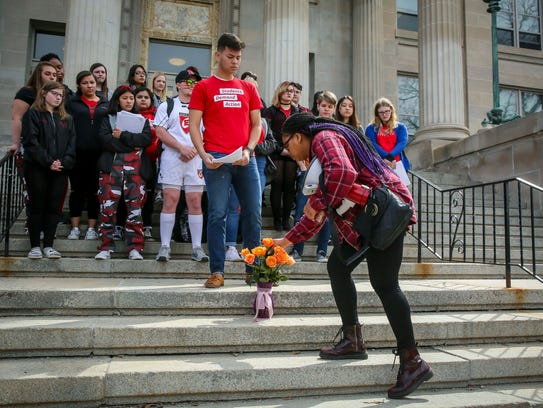 Des Moines East High students place roses in a vase