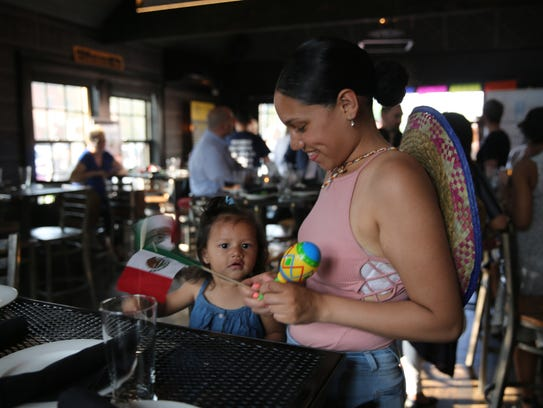 Marylou Rodriguez (right) plays with her 1-year-old
