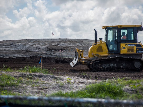 A bulldozer drives in front of what will be a grass-covered