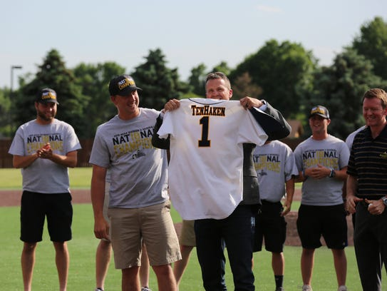Mayor Paul TenHaken is presented with a jersey by Sioux