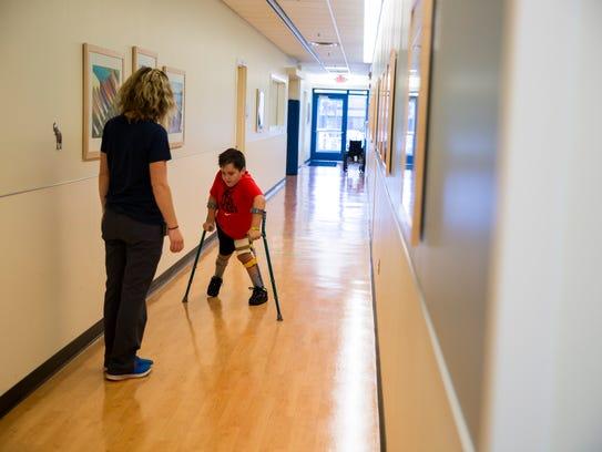 Therapist Kendra VanWasshenova helps Gabe Treve practice
