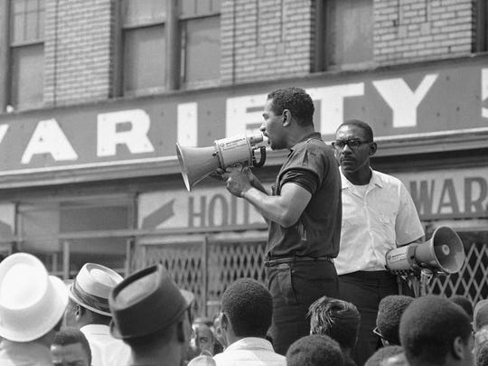 "Congressman John Conyers, Detroit Democrat, uses a bullhorn as he tried to encourage African Americans in Detroit's riot area to go home, July 23, 1967. He was met with shouts of ""No, no."" As Conyers stepped down a rock hit the street a few feet from him."