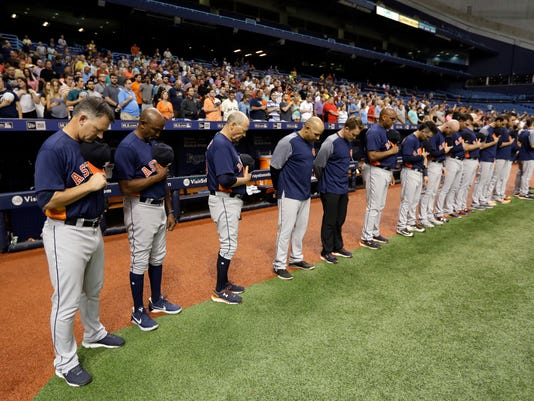 Members of the Houston Astros, including manager A.J. Hinch, left, take part in a moment of silence for the victims of Hurricane Harvey before a baseball game against the Texas Rangers on Tuesday, Aug. 29, 2017, in St. Petersburg, Fla. The Astros moved their three-game home series against the Rangers to St. Petersburg because of unsafe conditions from Harvey. (AP Photo/Chris O'Meara)