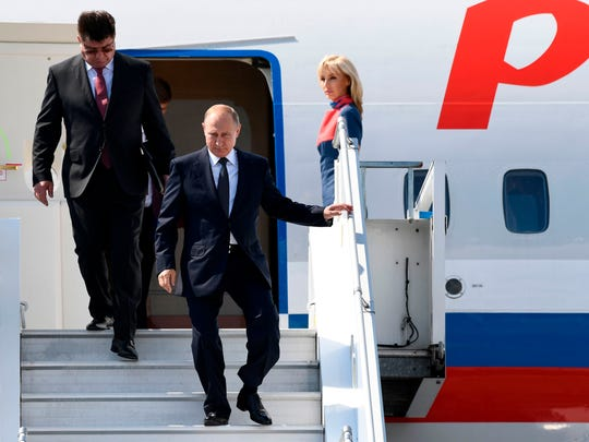 Russian President Vladimir Putin and Russia's new ambassador to Finland Pavel Kuznetsov disembark from an airplane upon arrival at Helsinki-Vantaa Airport in Helsinki Monday ahead of a summit with President Donald Trump.